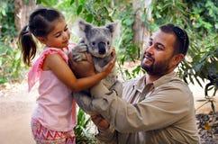 Gold Coast Queensland Australia. GOLD COAST, AUS - NOV 04 2014:Little girl (Talya Ben-Ari age 05) holding a Koala with Zookeeper in Currumbin Wildlife Sanctuary stock images
