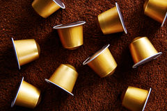 Gold coffee capsules on coffee background Royalty Free Stock Image