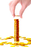 Gold coin. Someone add gold coin to coin tower stock image