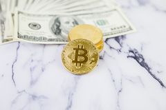 The gold coin bitcoin lies on a stack of hundred dollar bills. Crypto currency, physical coin. Exchange bitcoin for a dollar. Conc. Eptual image for worldwide royalty free stock photography