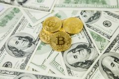The gold coin bitcoin lies on a stack of hundred dollar bills. Crypto currency, physical coin. Exchange bitcoin for a dollar. Conc. Eptual image for worldwide stock photo