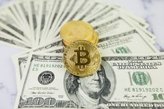 The gold coin bitcoin lies on a stack of hundred dollar bills. Crypto currency, physical coin. Exchange bitcoin for a dollar. Conc. Eptual image for worldwide royalty free stock images