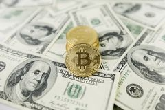 The gold coin bitcoin lies on a stack of hundred dollar bills. Crypto currency, physical coin. Exchange bitcoin for a dollar. Conc. Eptual image for worldwide royalty free stock image