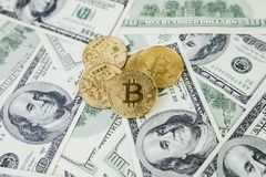 The gold coin bitcoin lies on a stack of hundred dollar bills. Crypto currency, physical coin. Exchange bitcoin for a dollar. Conc. Eptual image for worldwide stock photos
