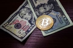 Large gold coin bitcoin and dollars. Gold coin bitcoin next to the bills of American dollars Stock Image