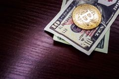 Large gold coin bitcoin and dollars. Gold coin bitcoin next to the bills of American dollars Stock Photography