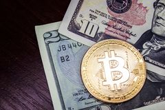 Large gold coin bitcoin and dollars. Gold coin bitcoin next to the bills of American dollars Royalty Free Stock Image