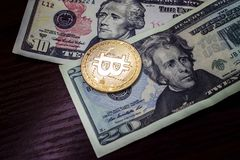 Large gold coin bitcoin and dollars. Gold coin bitcoin next to the bills of American dollars Stock Images
