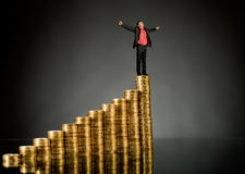 Gold coin. Businessman stand on top of  many rouleau gold  monetary  coin, on dark background Royalty Free Stock Photos