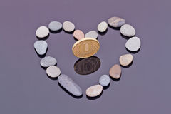 Gold coin in the center of heart of small sea stones Stock Photo