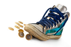 Gold coin rolled under the sneakers. Royalty Free Stock Image