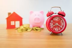 Gold coin,small house , piggybank and alarm clock Royalty Free Stock Image
