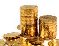 Gold coins. In a stacks isolated on white stock photography