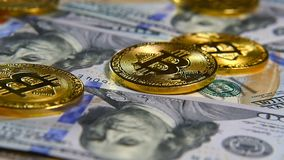 Gold coins of bitcoins and a background of hundred-dollar bills. The concept of financial operations. Economy of the. Gold coins of bitcoins and a background of stock footage