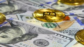 Gold coins of bitcoins and a background of hundred-dollar bills. The concept of financial operations. Economy of the. Gold coins of bitcoins and a background of stock video footage