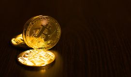Gold coins of bitcoins on an office table on a dark background. High resolution photo Stock Photos