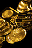 Gold Coins and Bullion for Wealth. Gold coins and bullion in a pile with dark background Stock Image