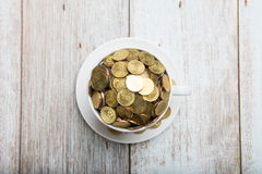 Gold coins on a coffee cup Stock Photography