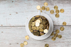 Gold coins on a coffee cup Stock Image