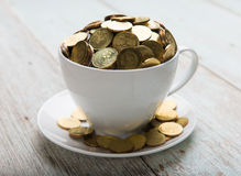 Gold coins on coffee cup Royalty Free Stock Image
