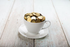 Gold coins on coffee cup Stock Photography