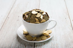 Gold coins on coffee cup Royalty Free Stock Photos
