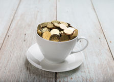 Gold coins on coffee cup Stock Image