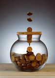 Gold coins dropping into glass jar Stock Images
