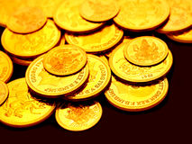 Gold coins embossed with images. Strewn around Stock Images