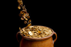 Gold coins falling in the vintage pot Stock Images