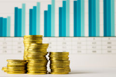 Gold coins with financial chart. Stacks of gold coins with financial chart as background Royalty Free Stock Images