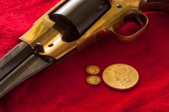 Gold Coins and Gun Stock Photography