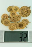 Gold coins on a jewelery scale Stock Image