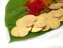 Gold coins kept on betel leaf. Many gold coins kept on betel leaf along with vermilion powder Stock Images