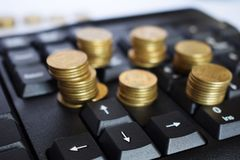 Gold coins on the keyboard, business concept stock photography
