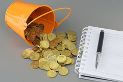 Gold Coins Notepad and Bucket - Business Concept Stock Photography