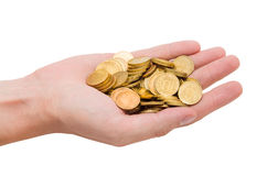 Gold coins on the palm of your hand. A handful of gold coins on the palm of your hand royalty free stock photo