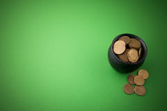 Gold coins in a pot on green background. Top view stock photography