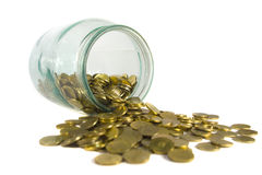 Gold coins spilling from a jar Royalty Free Stock Photos