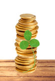 Gold coins stack and clover leaf on table isolated on white Royalty Free Stock Photography