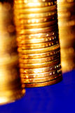Gold Coins Stacked. Stacks of gold coins on blue background Royalty Free Stock Photo