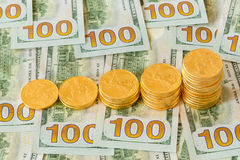 Gold coins stacked on new design 100 dollar bills Stock Photo