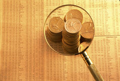 Gold coins on stock index under magnifying glass Royalty Free Stock Photos