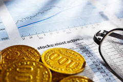 Gold coins and stock sheet Stock Photography