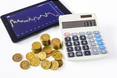 Gold coins and tablet placed on a white table showing a graph. Stock market trading. Calculation on Calculator. Watch the stock market on a tablet. Financial Royalty Free Stock Photo