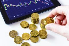 Gold coins and tablet placed on a white table showing a graph. Stock market trading. Watch the stock market on a tablet. Financial saving. Lots of Czech coins Royalty Free Stock Photo