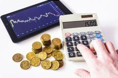 Gold coins and tablet placed on a white table showing a graph. Stock market trading. Calculation on Calculator. Watch the stock market on a tablet. Financial Royalty Free Stock Images