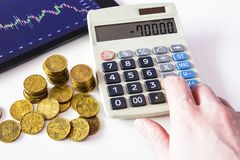 Gold coins and tablet placed on a white table showing a graph. Stock market trading. Calculation on Calculator. Watch the stock market on a tablet. Financial Royalty Free Stock Photography