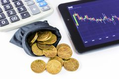 Gold coins and tablet placed on a white table showing a graph. Stock market trading. Calculation on Calculator. A black bag full of coins. Watch the stock Royalty Free Stock Images