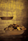 Gold coins on weighing scales Royalty Free Stock Photography